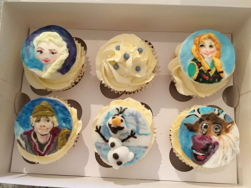 Character cupcakes. Vanilla cupcakes topped with piped vanilla buttercream with hand-painted sugar plaques.