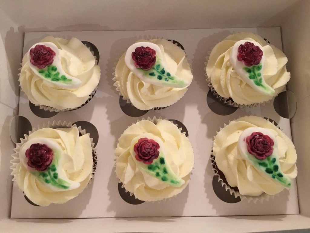 Cupcakes with vanilla flavoured buttercream, topped with moulded, hand-painted dark red rose sugar decorations