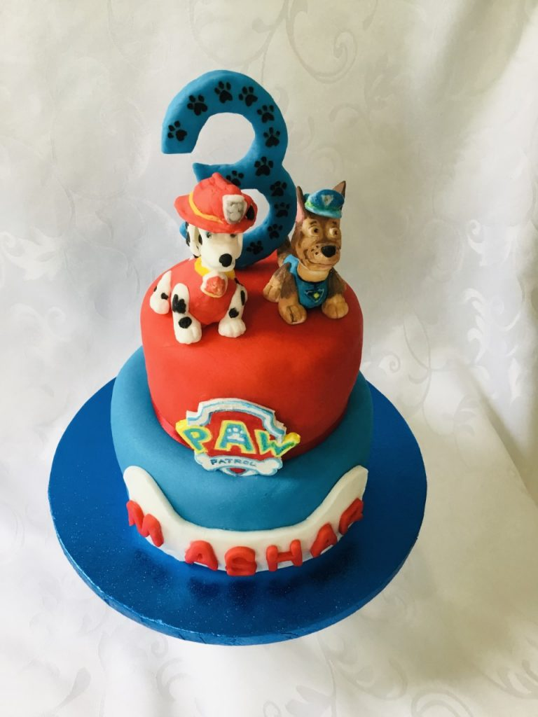 A 2 tier birthday cake, the lower with blue icing, the upper with red. The upper tier is topped with two cartoon style dogs and a number three. The lower tier has a child's birthday dedication on the front facing side.